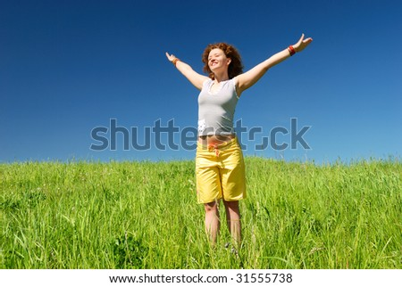 Girl stretching hands on the field under sun - stock photo