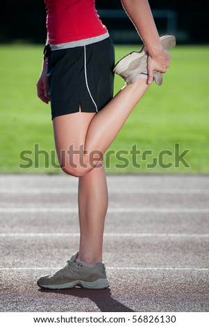 Girl stretching on a running track - side view - stock photo
