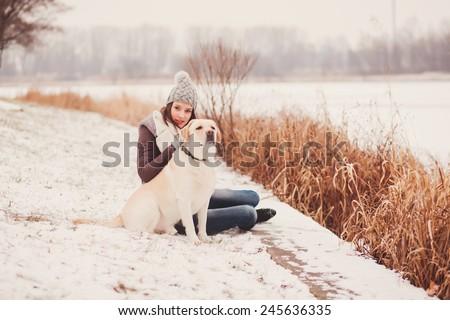 Girl stroking dog in winter park - stock photo