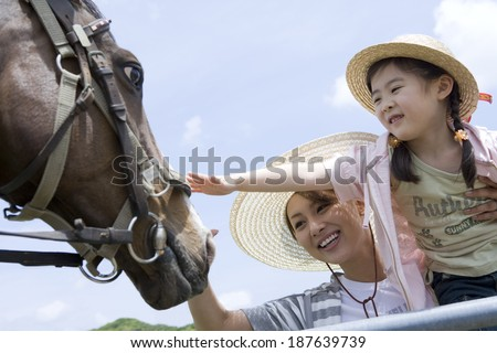 girl stroking horse and mother watching her - stock photo