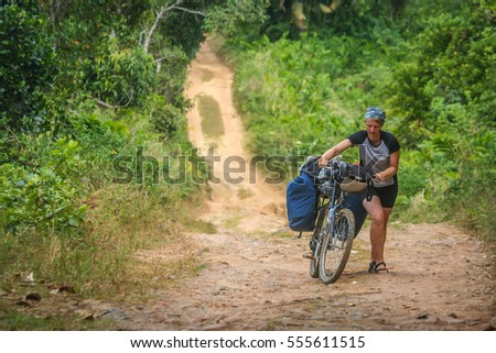 Girl struggling with her bike on a steep, rocky jungle road to Maroantsetra on the Vanilla Coast in Madagascar