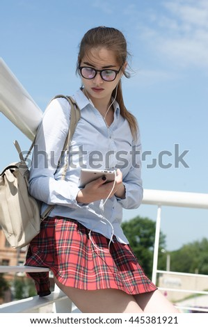 Girl student holds in hands of a tablet.