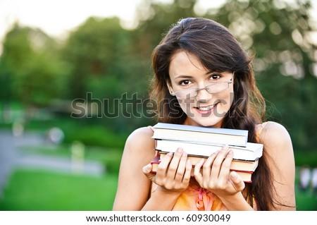 Girl-student holds textbooks, against summer garden. - stock photo