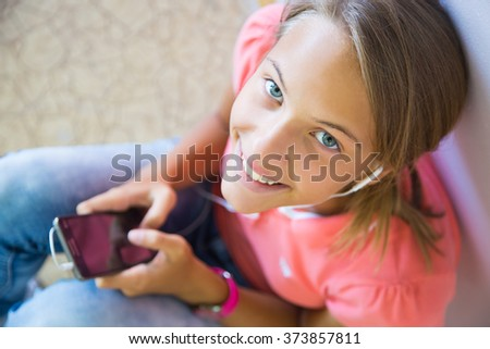 Girl student playing with the phone and smiling - stock photo