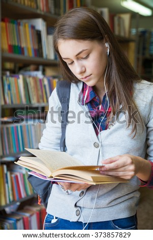 Girl student reads a book at the library - stock photo