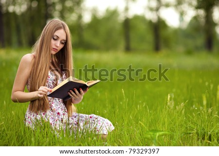 Girl-student sit on lawn and reads textbook. - stock photo