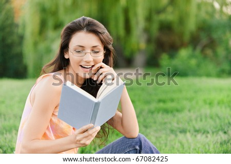Girl-student sits on lawn and reads textbook. - stock photo