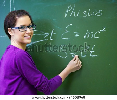 girl student wearing glasses at the blackboard writing formula - stock photo