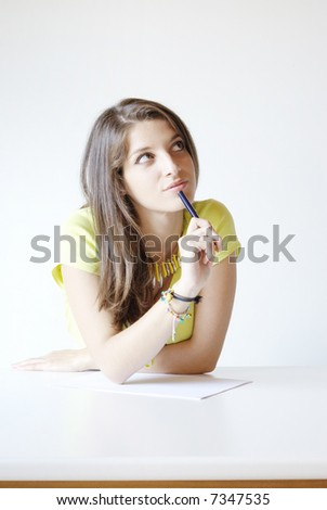 Girl student writes the exercise of the examinations paper - stock photo