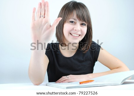 Girl student writes the exercise of the examinations showing her hand - stock photo