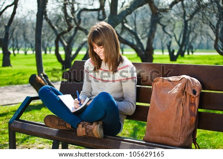 girl studying and writing in a park - stock photo