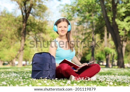 Girl studying in park and listening to a music seated in a field full of flowers - stock photo