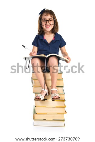 Girl studying on a pile of books - stock photo