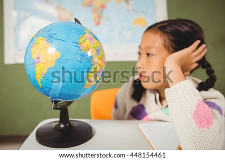 Girl studying the globe at school