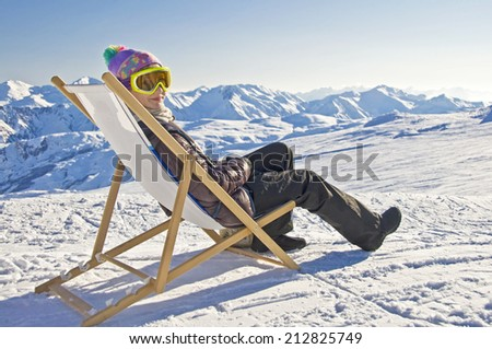 Girl sunbathing in a deckchair on the side of a ski slope, snowy mountain landscape - stock photo