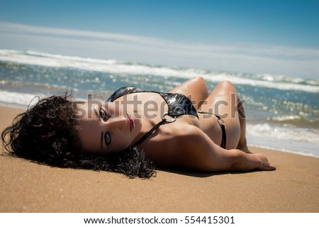 Girl sunbathing, lying on beach in black bikini. Ocean in the background with blue skies.