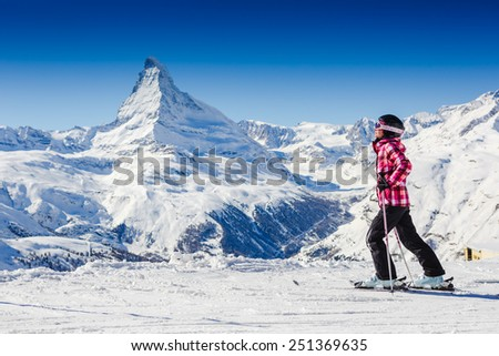 girl sunbathing near a snowy ski slope with blue sky background. Matterhorn. Swiss Alps  - stock photo