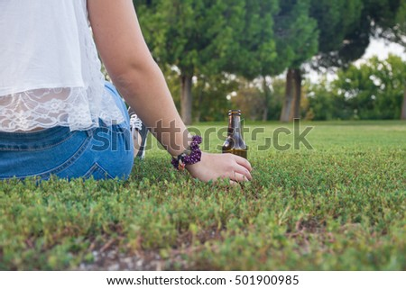 Girl supports his beer bottle on the floor while looking at the horizon thoughtfully. It is a photo close where his hand and beer resting on the grass looks.