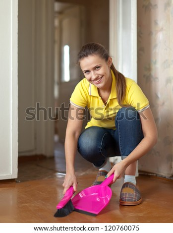 Girl sweeps the floor at home - stock photo