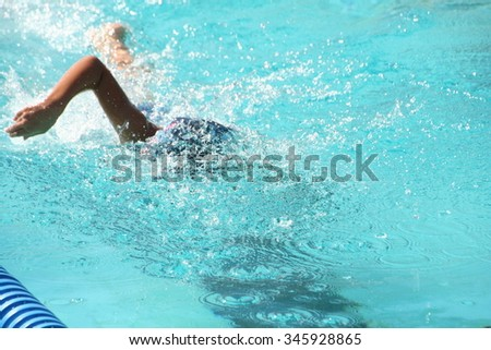 girl swimming freestyle at swim meet - stock photo