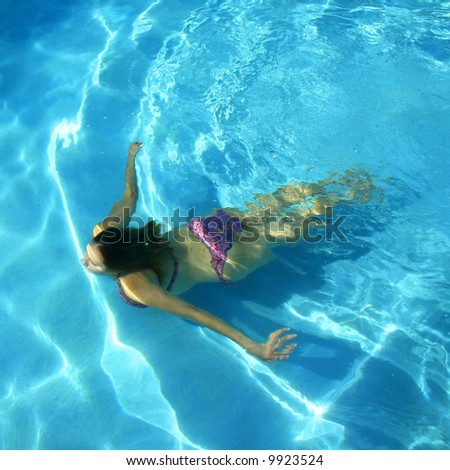 Girl swimming underwater in a swimming pool - stock photo