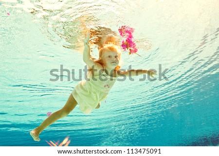 girl swimming underwater on pool - stock photo