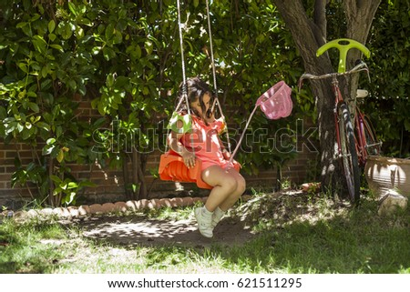 Girl swinging at the playground. Garden. Nature. Games