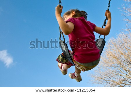 girl swings high into a blue sky with copyspace