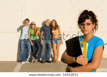 girl swot being jeered at by other students - stock photo