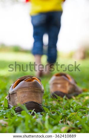 Girl take off her leather shoes. Child's foot learns to walk on grass, reflexology massage. child relax in garden. Shallow depth of field (dof), selective focus. - stock photo