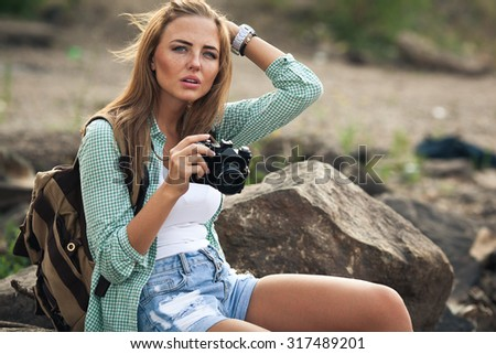 Girl takes photographs with vintage photo camera outdoor - stock photo