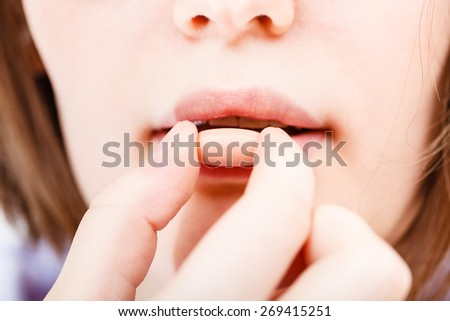 girl takes tablet close up - stock photo