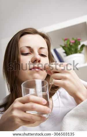 girl takes the pill with water - stock photo