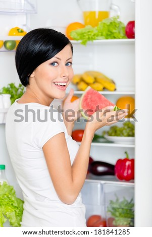 Girl takes watermelon from the opened fridge full of vegetables and fruit. Concept of healthy and dieting food
