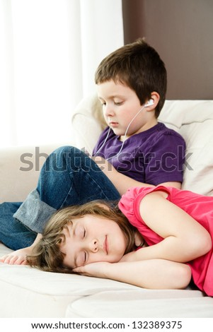 Girl taking a nap while her brother listen to music