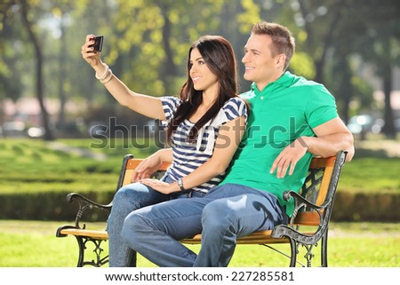 Girl taking a selfie with her boyfriend in park seated on a wooden bench  - stock photo
