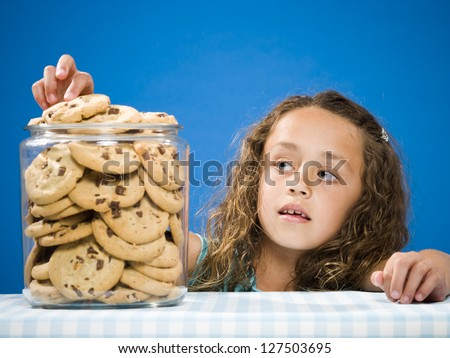 Girl taking chocolate chip cookie from jar - stock photo