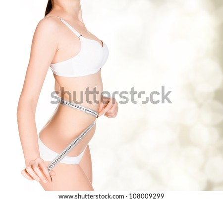 girl taking measurements of her body, golden blurred background with a space for your message or graphics - stock photo