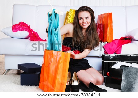 Girl taking new dress out of the shopping bag - stock photo