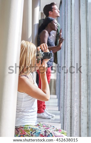 Girl taking photo out of window with people in background
