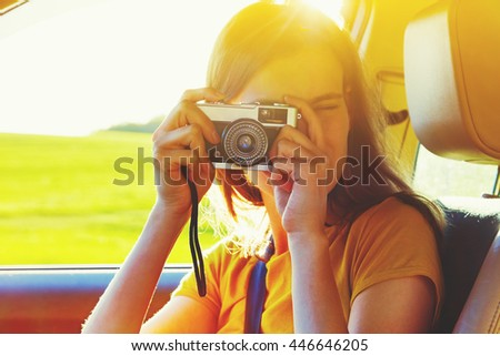 girl taking photo with camera moving in car - stock photo