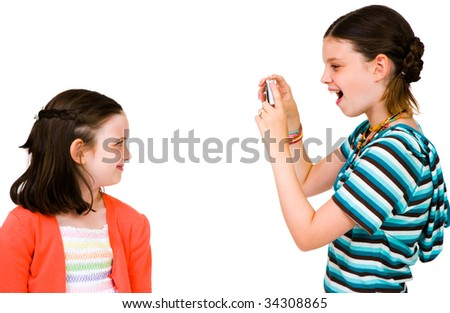 Girl taking picture of her sister with a camera isolated over white - stock photo