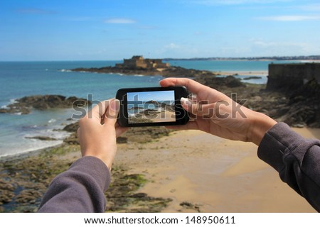 Girl taking pictures on a mobile phone in the Fort on island Petit Be in Saint-Malo - stock photo