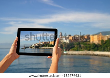 Girl taking pictures on a tablet in Bastia, Corsica, France.