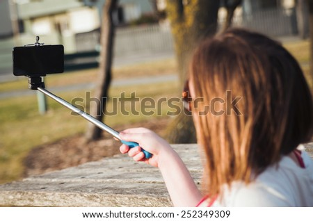 girl taking selfie picture outdoors.Focus on phone - stock photo