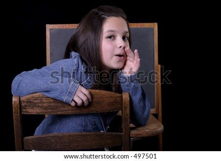 Girl talking at desk with blackboard in background