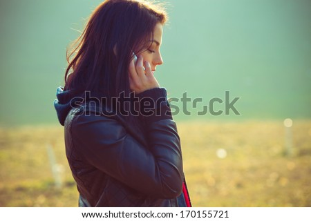 girl talking on mobile phone outdoor shot profile - stock photo