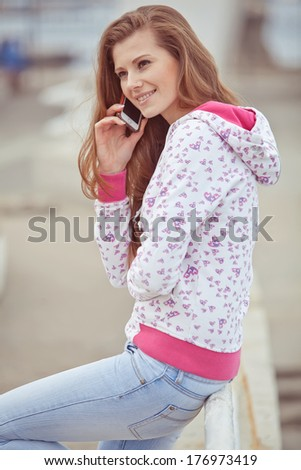 Girl talking on the phone outdoors - stock photo