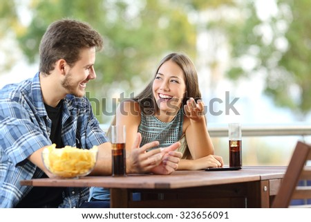 Girl talking with a friend in a terrace with snacks and drinks - stock photo