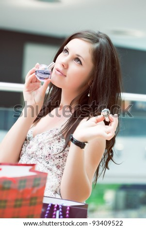girl tastes a smell just the spirits bought in shopping center - stock photo